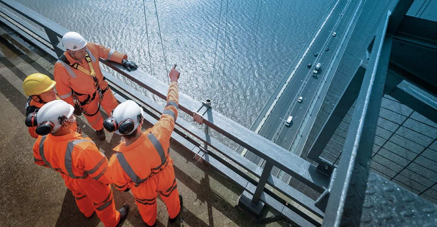 visual of four worker socotec on a bridge